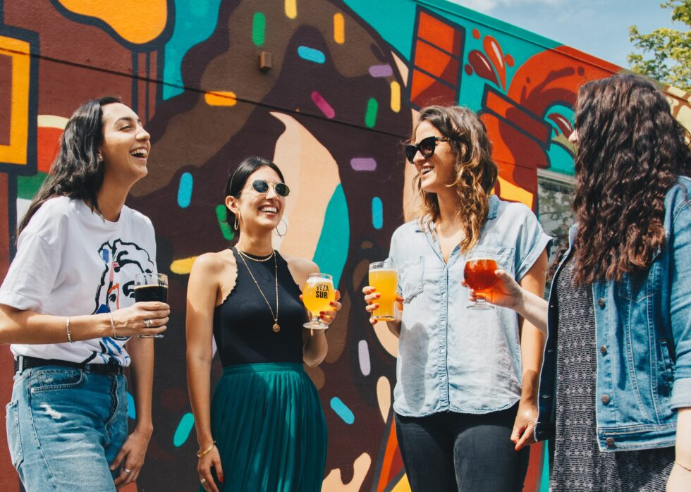 four young women hanging out and smiling with drinks at a local business