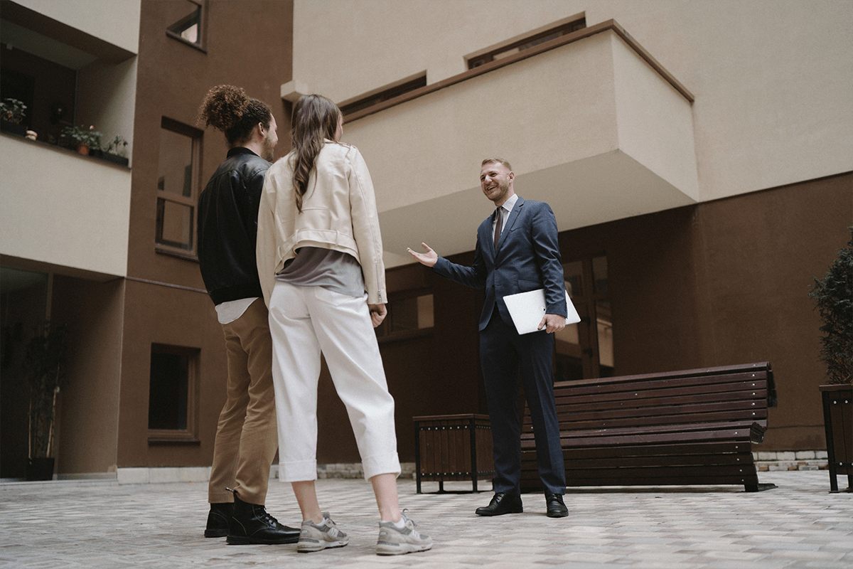 couple speaking to a real estate agent about buying property