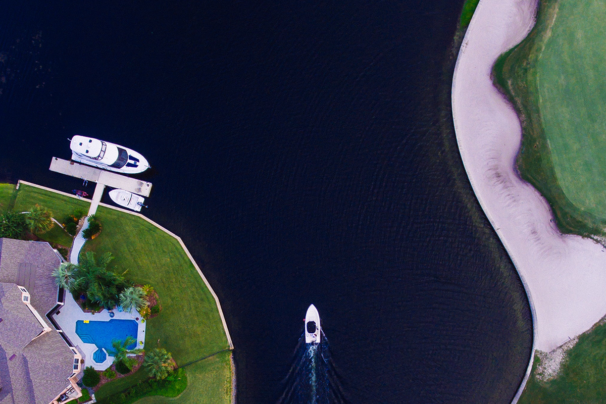 drone view of boat on blue water passing luxury waterfront homes