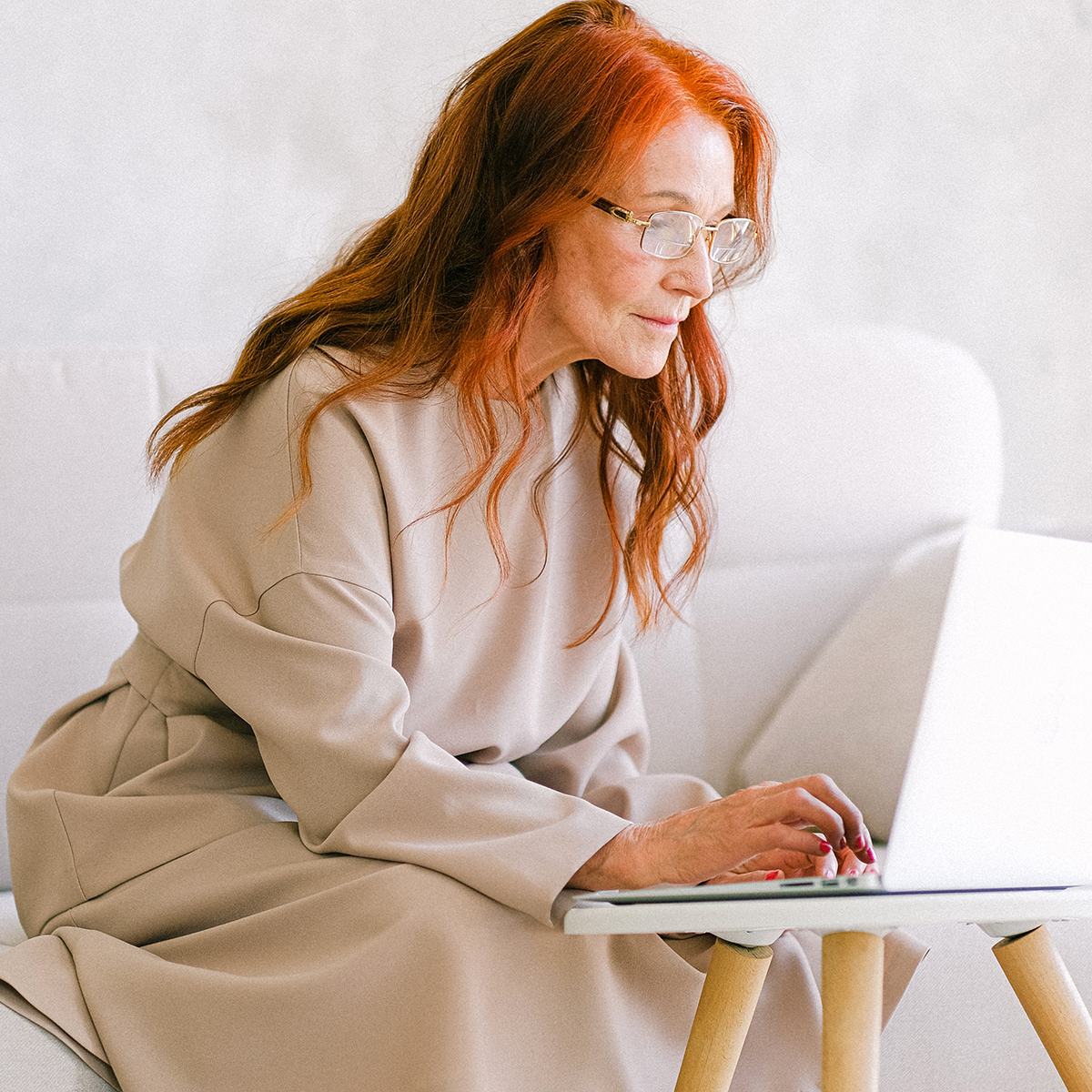 woman looking at luxury homes for sale on laptop