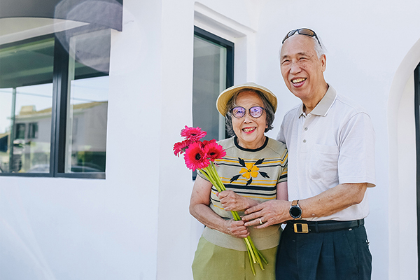 senior couple smiling in front of their home