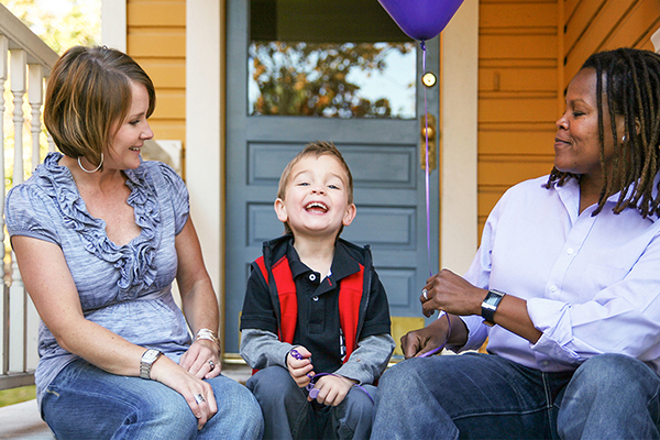women sitting on a front porch with a happy little boy